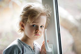 Little girl standing by the window — Stockfoto