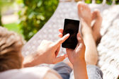 Man using mobile smart phone while relaxing in a hammock — Stock Photo
