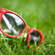 Red sunglasses in green grass — Stock Photo