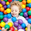 A young blond girl child having fun playing with colorful plastic balls — Stock Photo #27704927