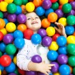 A young blond girl child having fun playing with colorful plast — Stock Photo #27705409