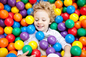 A young blond girl child having fun playing with colorful plastic balls — Stock Photo