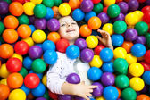 A young blond girl child having fun playing with colorful plast — Stock Photo