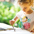 Portrait of little girl painting, summer outdoor — Stock Photo