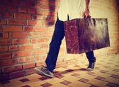 Young man walking along street with old suitcase, retro tinted — Stock Photo