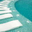 Empty sunbeds by the beautiful resort pool — Stock Photo