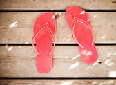 Pink flip flop sandals on wood background — Stock Photo