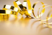 Golden ribbon on golden background — Stock Photo