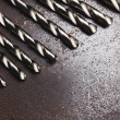 Twist drill bits on old metal texture — Stock Photo