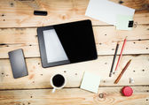 Workplace, tablet pc and smart phoned on wooden table — Stock Photo