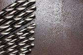 Twist drill bits on old metal texture — Stock Photo