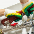 Stock Photo: Worker hands fixing heating system