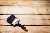 Hand met grote penseel over hout achtergrond — Stockfoto