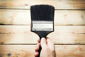 Hand holding big paintbrush over wood background — Zdjęcie stockowe