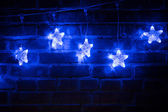 Christmas blue lights garland on a brick wall — Stock fotografie