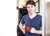 Man at home, drinking coffee or tea near window — Stock Photo