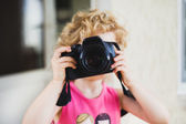 Little girl taking picture with SLR camera  — Stockfoto