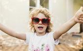 Cute dziewczynka w czerwone okulary wyświetlane kciuki — Zdjęcie stockowe