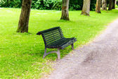 Stylish bench in summer park — Stock Photo