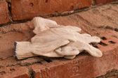 Tyg handskar på tegelstenar — Stockfoto