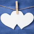 Two blank white hearts over wood wall — Stock Photo