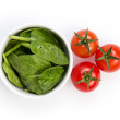 Fresh spinach leaves in bowl and tomatoes — Stock Photo #21586917