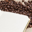 Heap of coffee beans on burlap and notepad — Photo