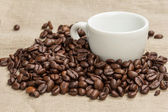 Heap of coffee beans on burlap with cup — Stock Photo