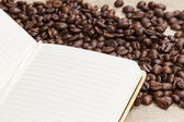 Heap of coffee beans on burlap and notepad — Stock Photo