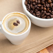 Espresso in a cup and cup full of beans - Stock Photo