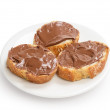 Stock Photo: Baguette slices spread with nut-choco paste on plate