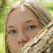 Portrait of young teenager girl hiding behind tree — Stock Photo