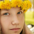 Portrait of young teenager girl on bench with wreath of dandelions — Stock Photo