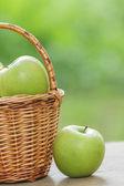 Green apples in a wicker basket — Stock Photo