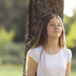Young girl leaning on a tree — Stock Photo