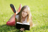 Young girl reading book lying on the grass — Stock Photo