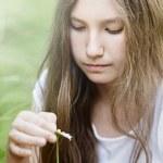 Teenage girl wonders on flower — Stock Photo #29190543