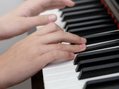 Close up photo of girls hands playing on piano — Stock Photo