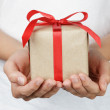 Young female hands holding gift — Stock Photo