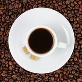 Cup of coffee in coffee beans — Stock Photo