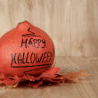 Happy Halloween inscription on the pumpkin with leaves — Stock Photo