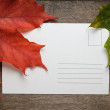 Autumn maple leaves on wood surface with paper card — Stock Photo