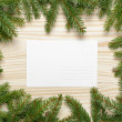 Christmas background from fir twigs with postcard — Stock Photo