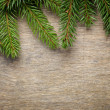 Christmas background from fir twigs on wooden table — Stock Photo