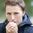 Young man warming hands with breathe — Stock Photo