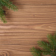 Green spruce twig on wooden plank — Stock Photo #34156771