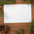 Green spruce twig on wooden plank witc greeting card — Stock Photo