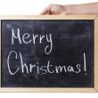 Female teen hand holding chalkboard with Merry Christmas text — Stock Photo