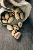Roasted and salted pistachios pour out of the bag — Stock Photo
