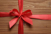 Tied ribbon bow on wood plank — Stock Photo
